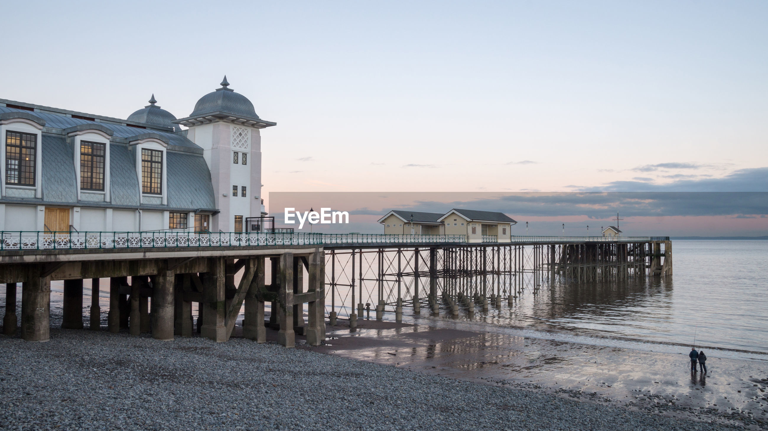PIER ON SEA AGAINST BUILDINGS DURING SUNSET