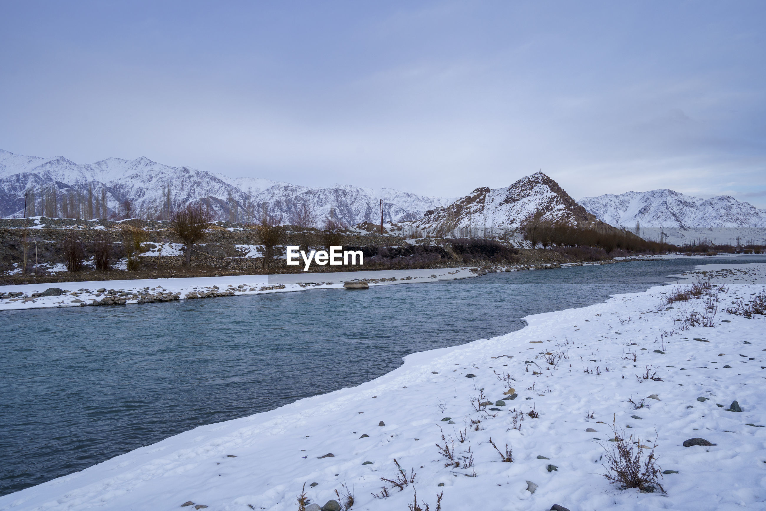 SCENIC VIEW OF FROZEN SNOWCAPPED MOUNTAINS AGAINST SKY