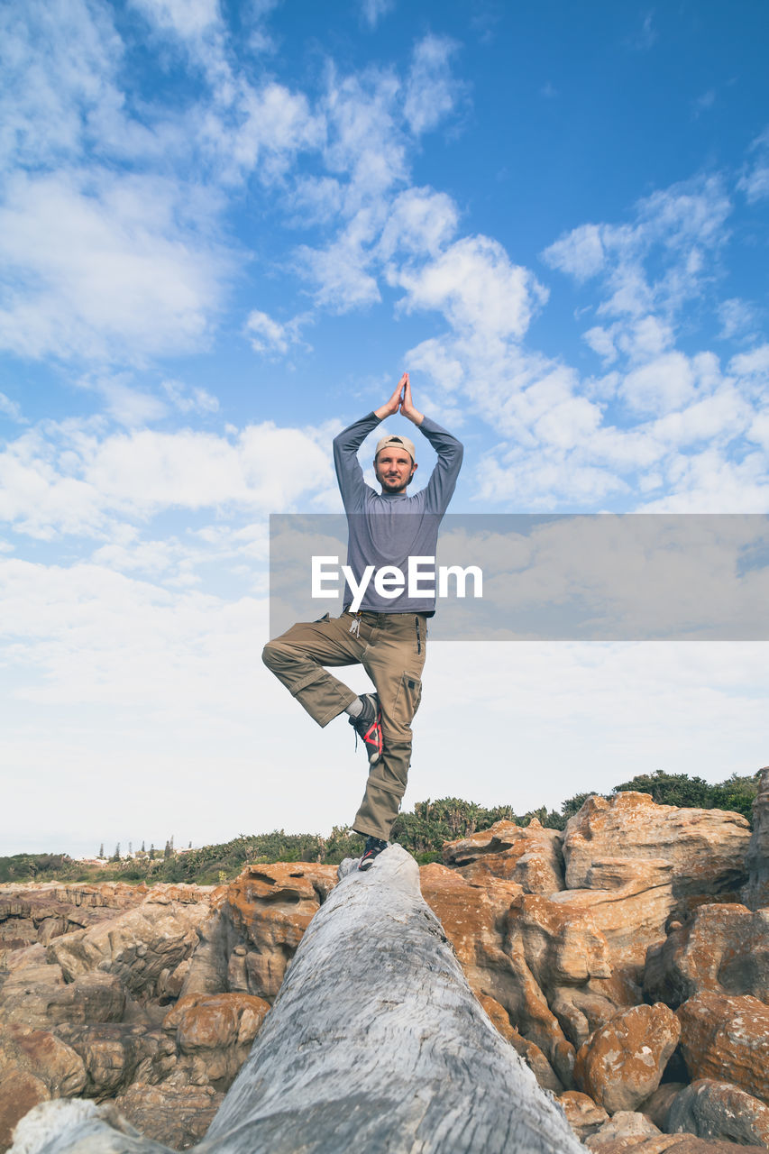 Full length of young man doing yoga on log against cloudy sky