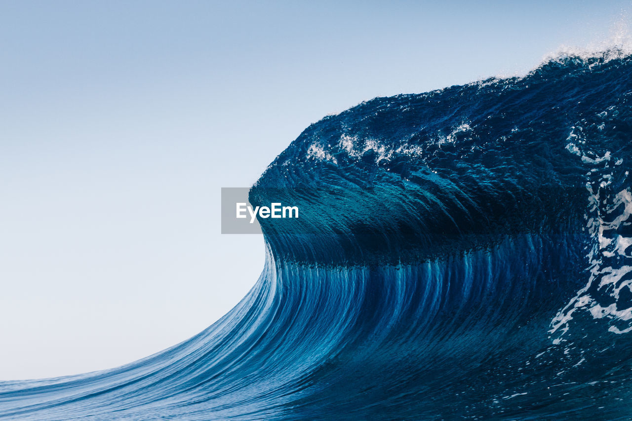 Scenic view of sea wave against clear blue sky