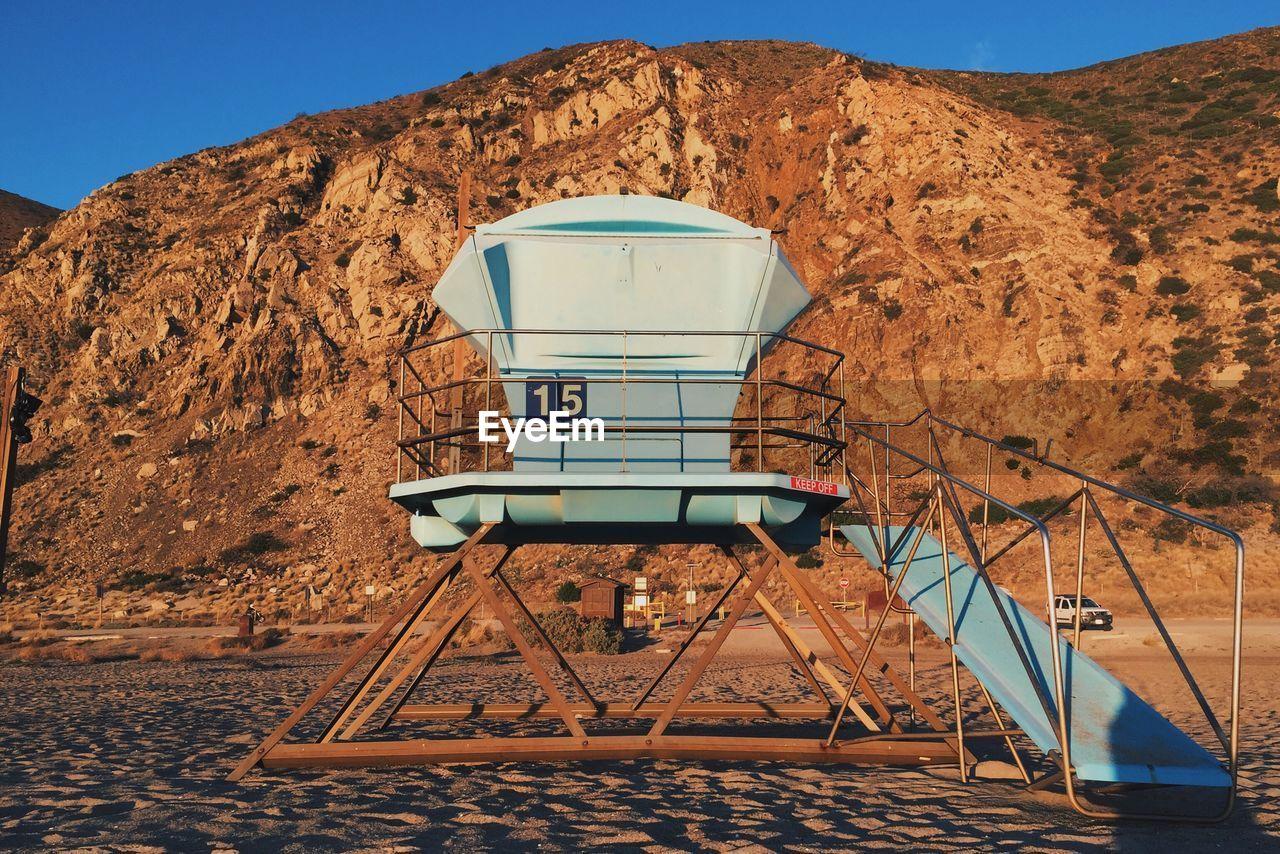 Lifeguard Hut Against Rocky Mountain At Sandy Beach
