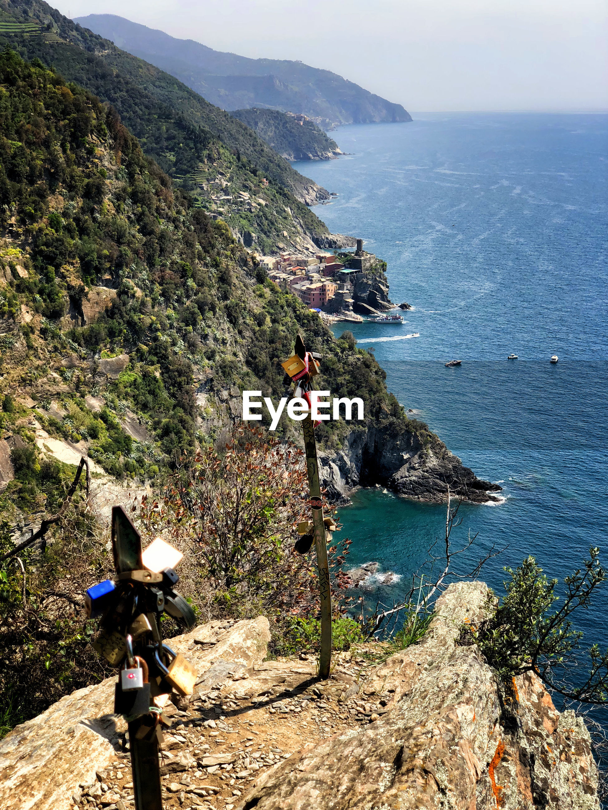 HIGH ANGLE VIEW OF PEOPLE LOOKING AT SEA AGAINST MOUNTAIN