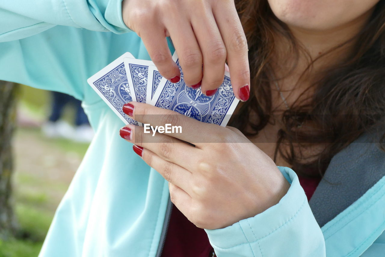 Midsection of woman playing cards
