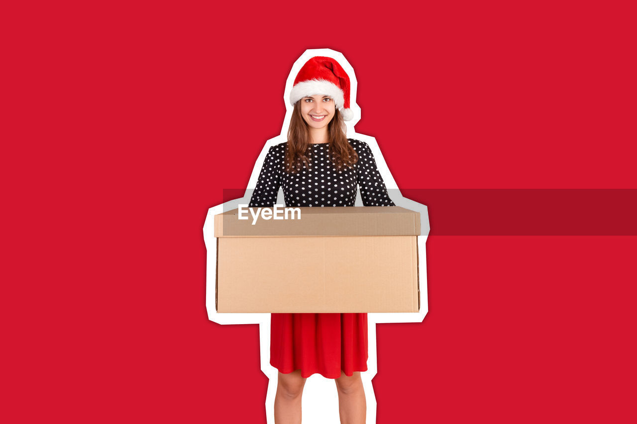 Portrait of smiling young woman holding cardboard box against red background