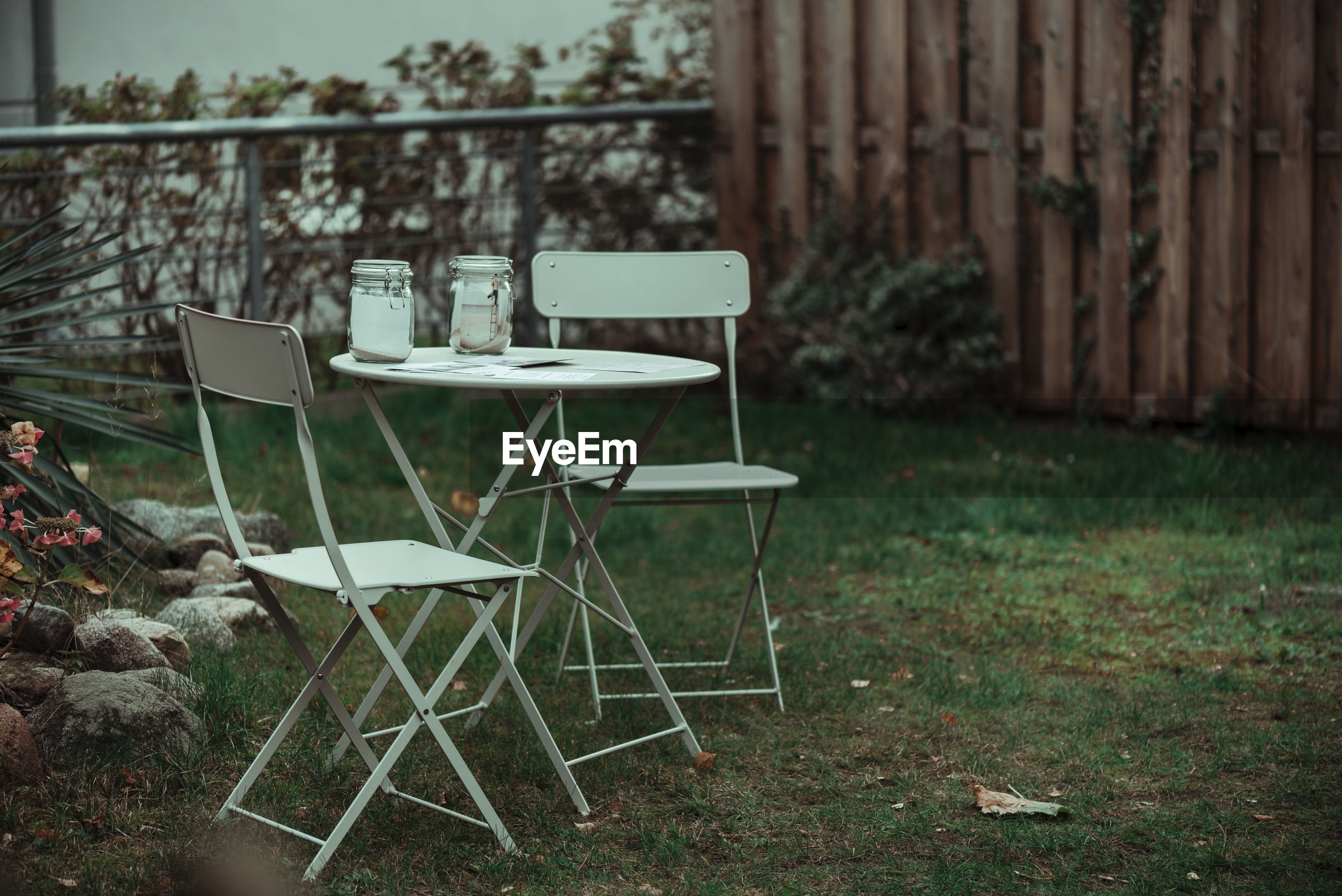 EMPTY CHAIRS AND TABLE ON LAWN