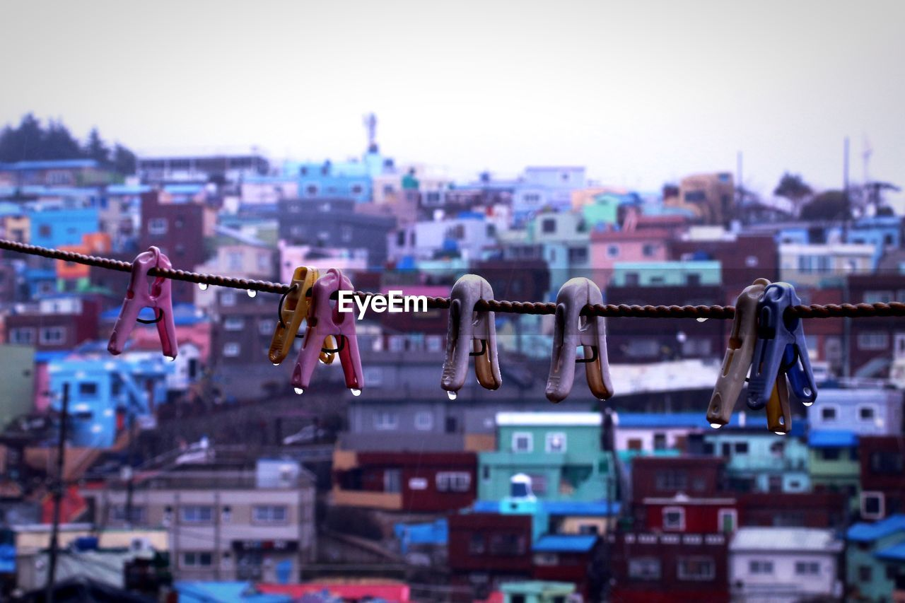 Close-Up Of Clothespins Hanging On Rope Against Cityscape