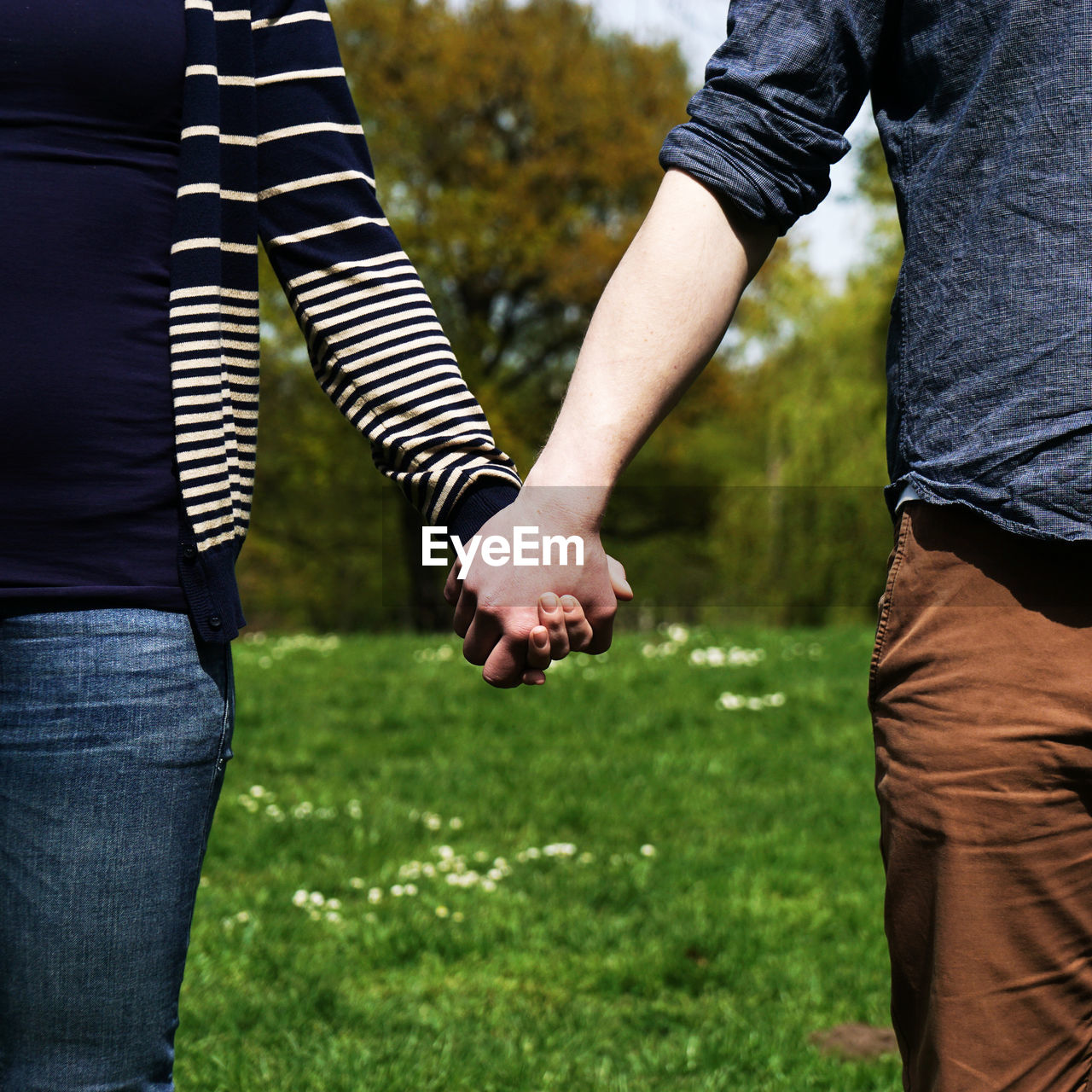 Midsection Of Young Couple Holding Hands In Park