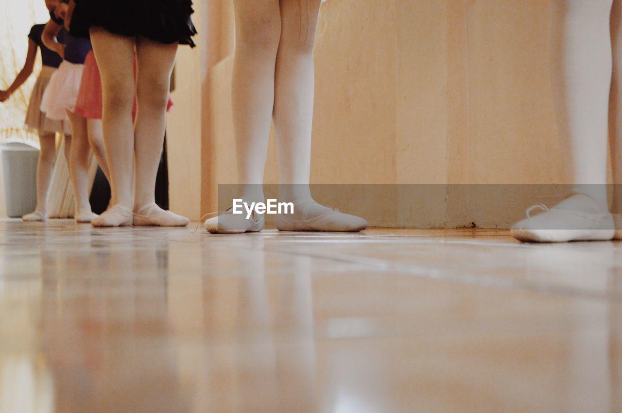Low Section Of Ballet Dancers Standing On Floor
