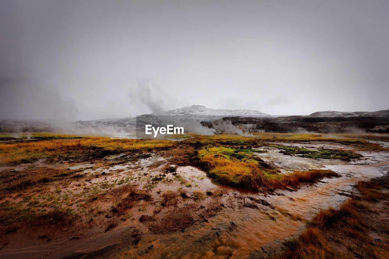 Scenic view of steam emitting from geyser