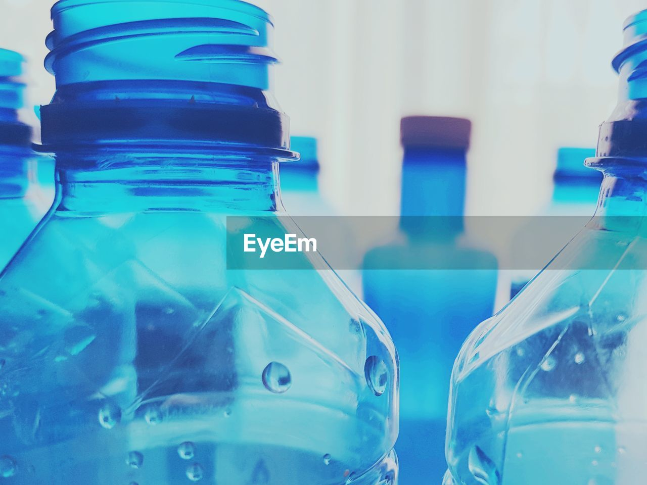 container, transparent, glass - material, bottle, indoors, close-up, focus on foreground, blue, no people, laboratory, science, still life, selective focus, plastic, research, food and drink, water bottle, drink, in a row, turquoise colored