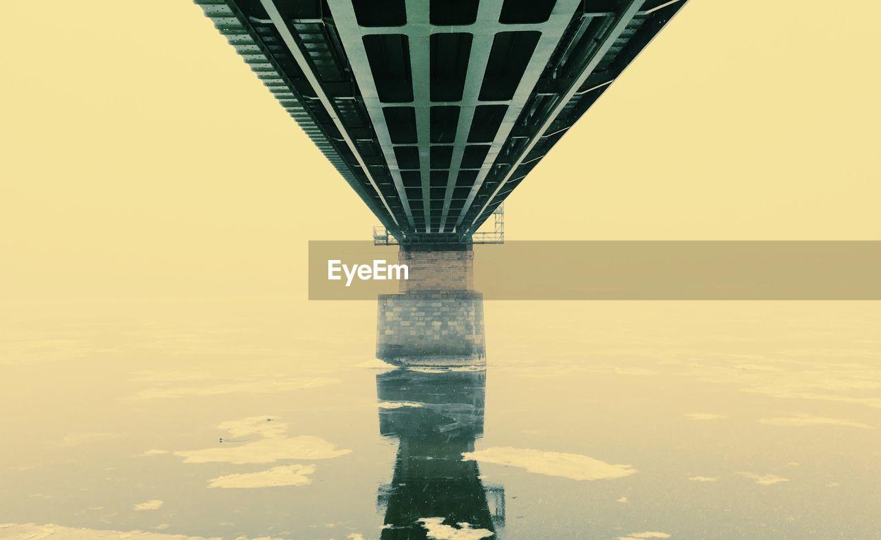 Bridge over sea against clear sky