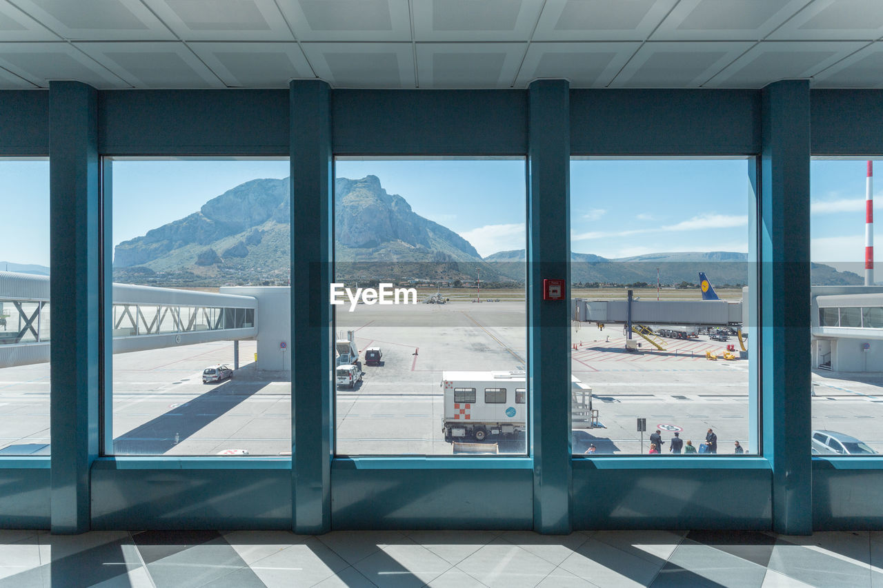 mountain, mountain range, day, window, transportation, indoors, airport, sky, real people, built structure, nature, architecture, water, beauty in nature