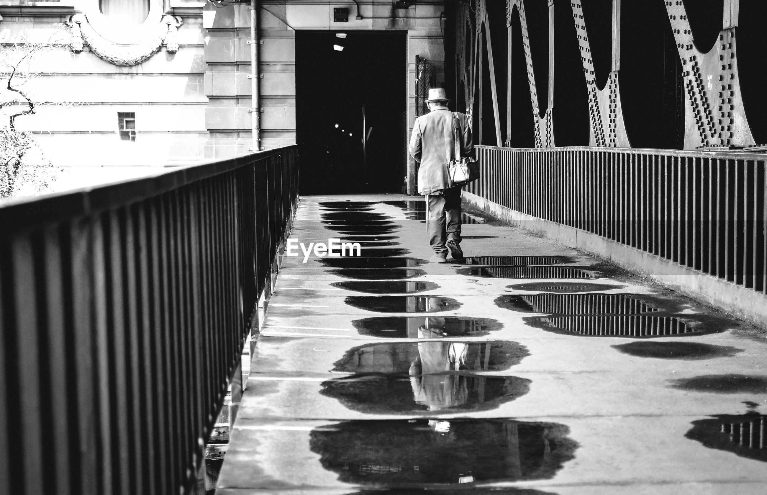 Rear view of man walking on wet footbridge