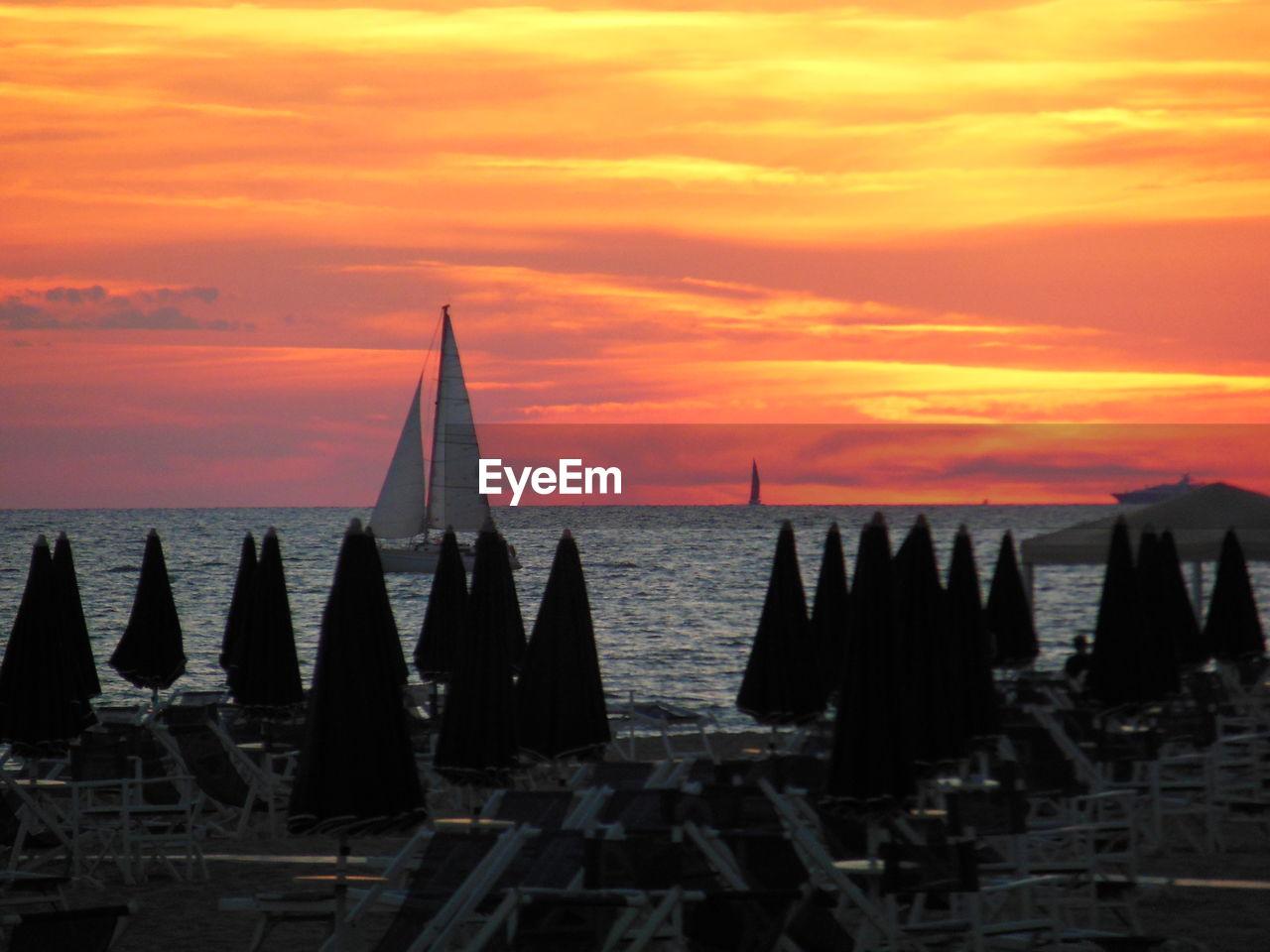 Silhouette parasols by sea against orange sky