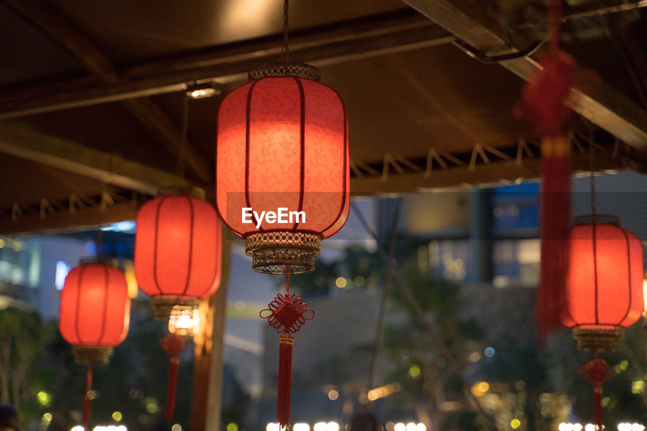 lighting equipment, lantern, illuminated, hanging, chinese lantern, focus on foreground, low angle view, no people, decoration, built structure, architecture, outdoors, red, ceiling, orange color, in a row, nature, chinese new year, paper lantern, chinese lantern festival, electric lamp