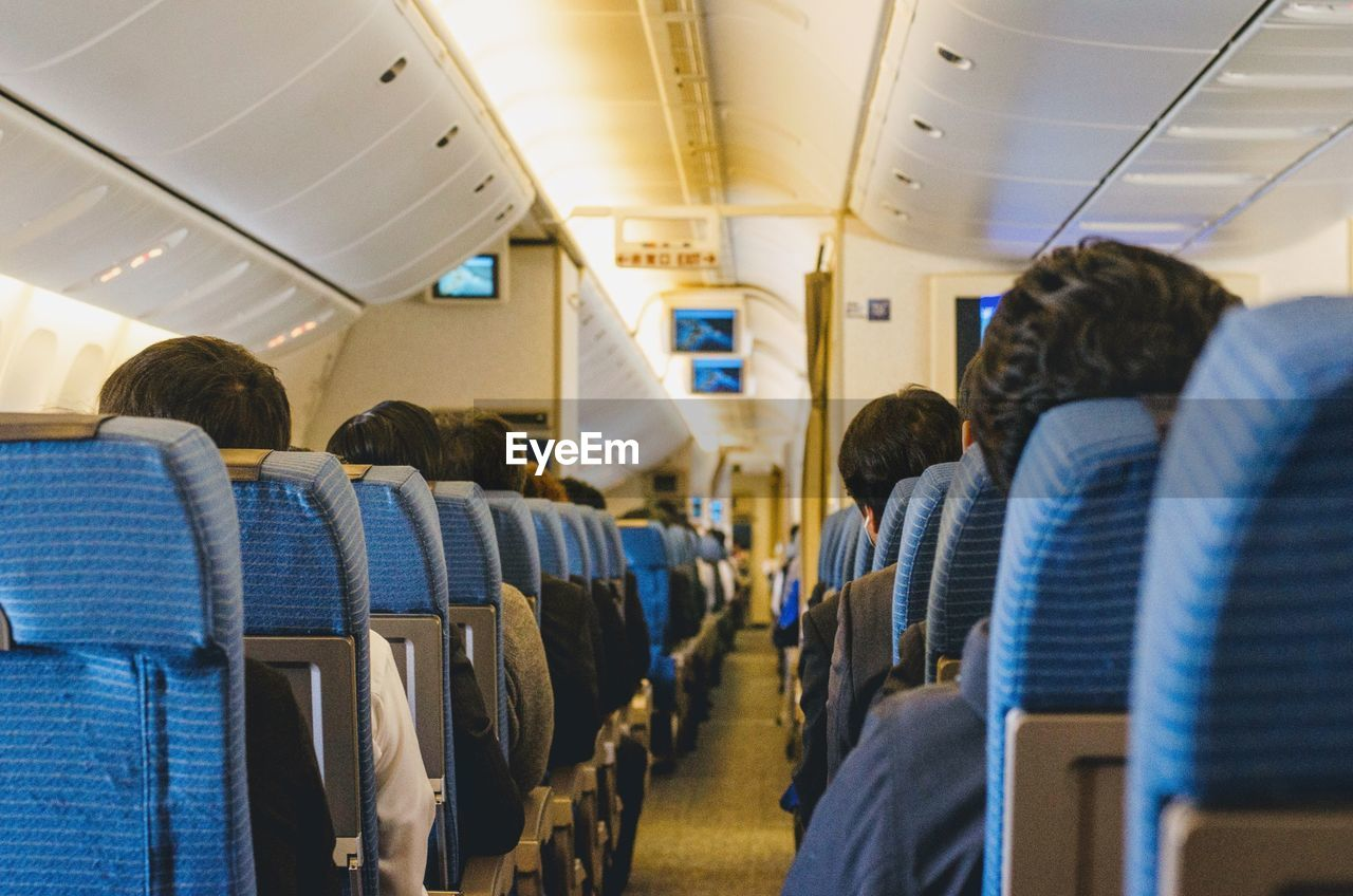 Rear View Of Passengers Sitting In Airplane