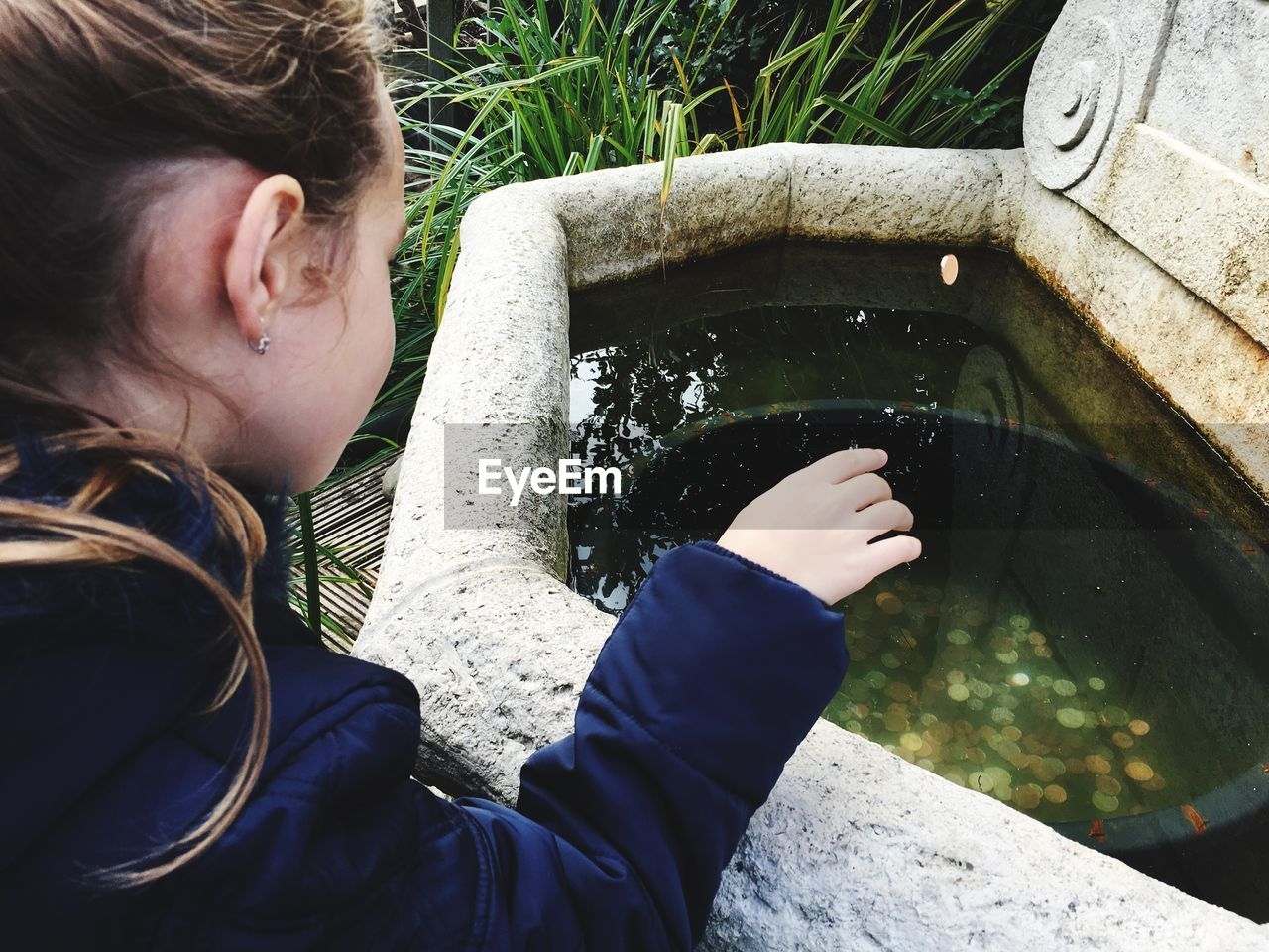 High Angle View Of Girl Throwing Coin In Wishing Well