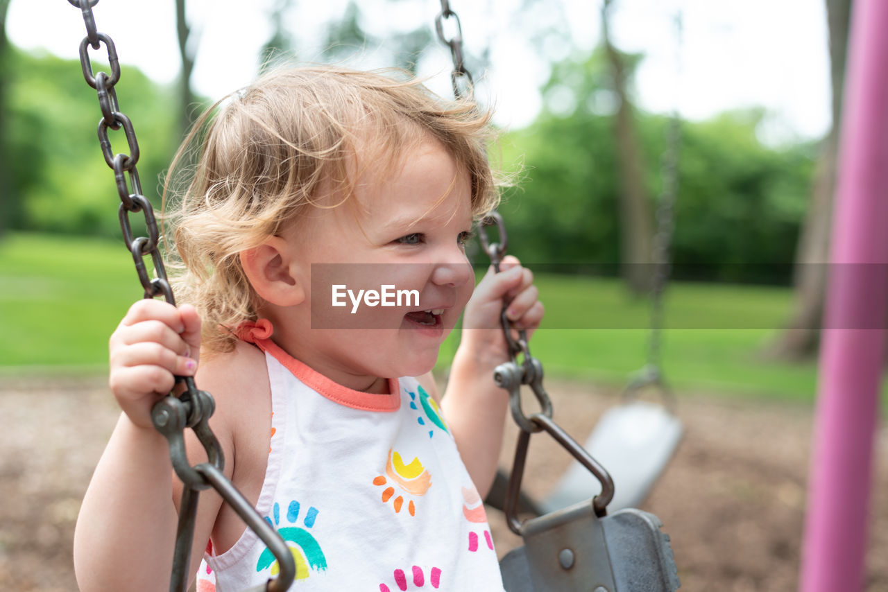 Cute girl looking away while sitting on swing