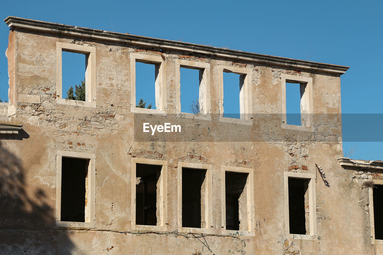 architecture, built structure, building exterior, sky, window, no people, building, low angle view, abandoned, nature, clear sky, sunlight, day, old, damaged, outdoors, history, blue, bad condition, weathered, ruined, archaeology
