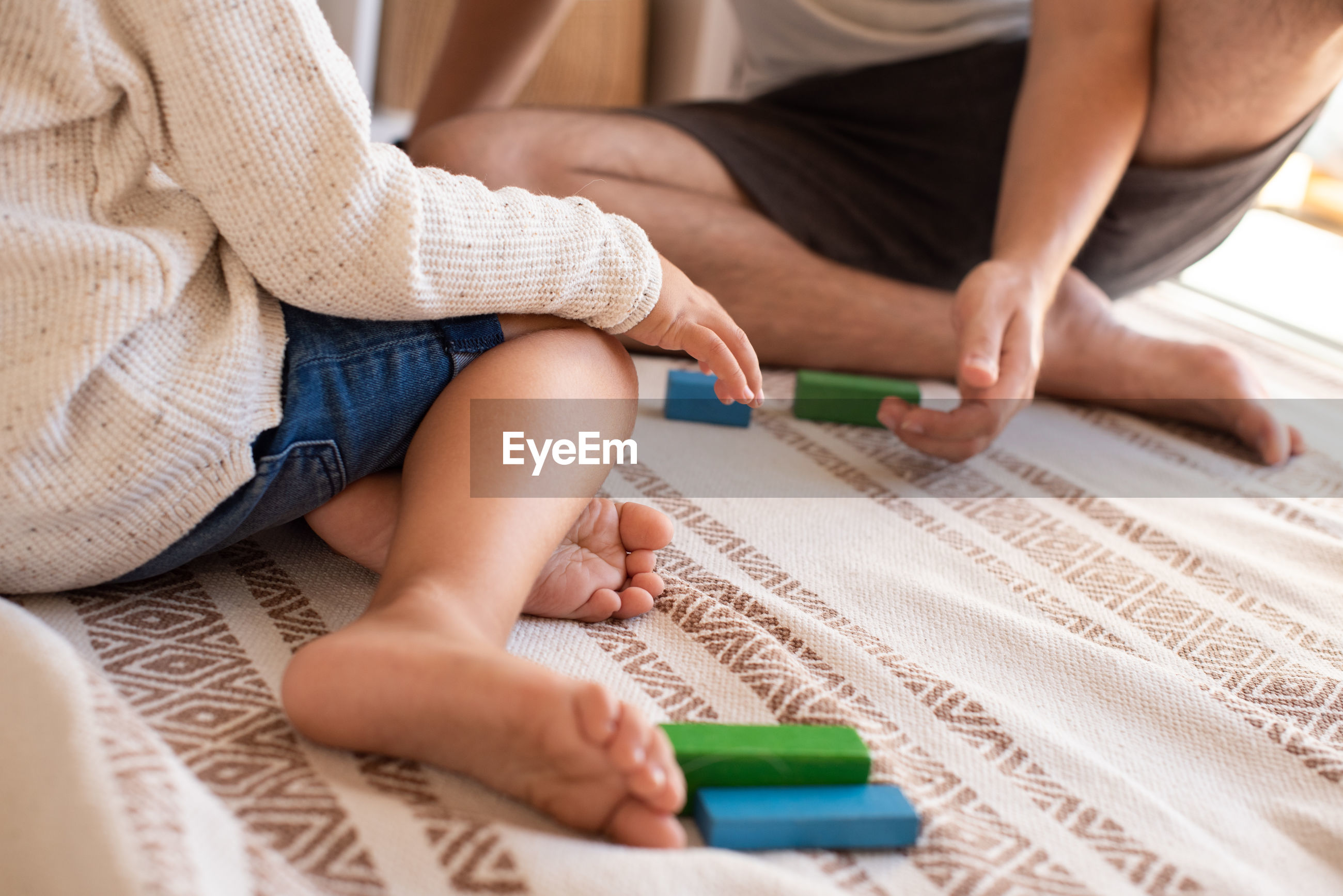 Low section of father and daughter playing with toy blocks on bed at home