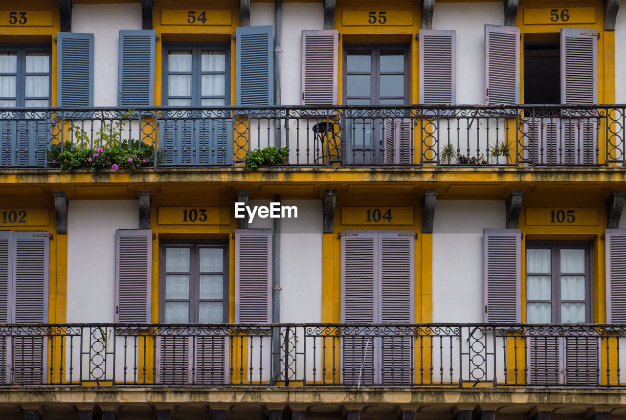 building exterior, architecture, built structure, window, balcony, outdoors, yellow, no people, residential building, day, plant