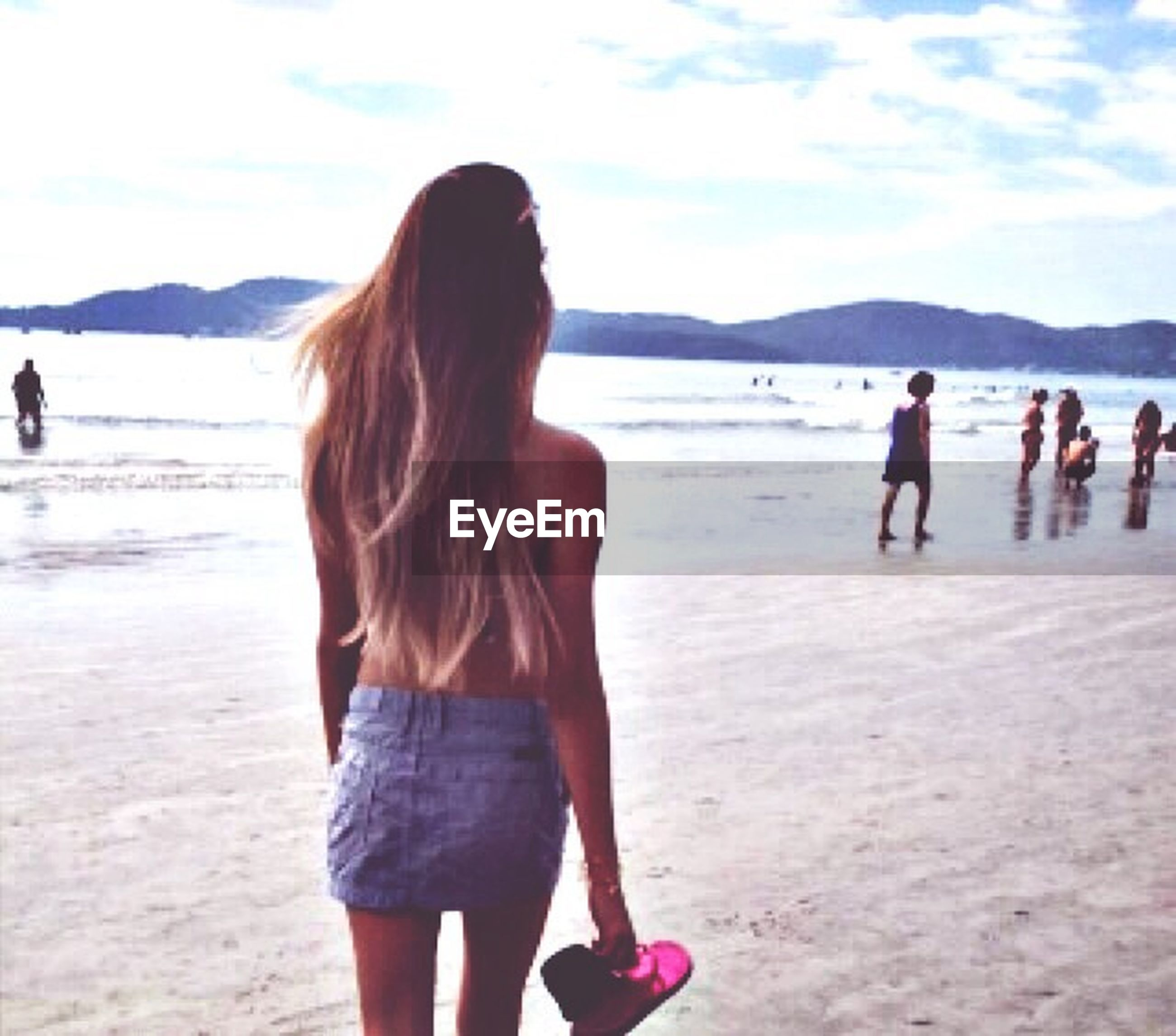 beach, sea, lifestyles, water, mountain, leisure activity, sky, person, vacations, sand, shore, scenics, standing, tourist, young women, beauty in nature, rear view, long hair