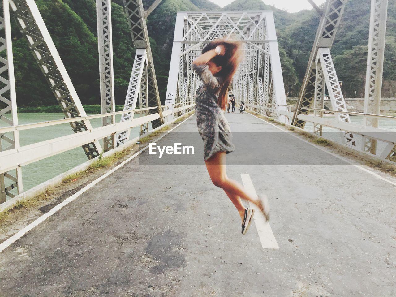 Full length of woman jumping on bridge