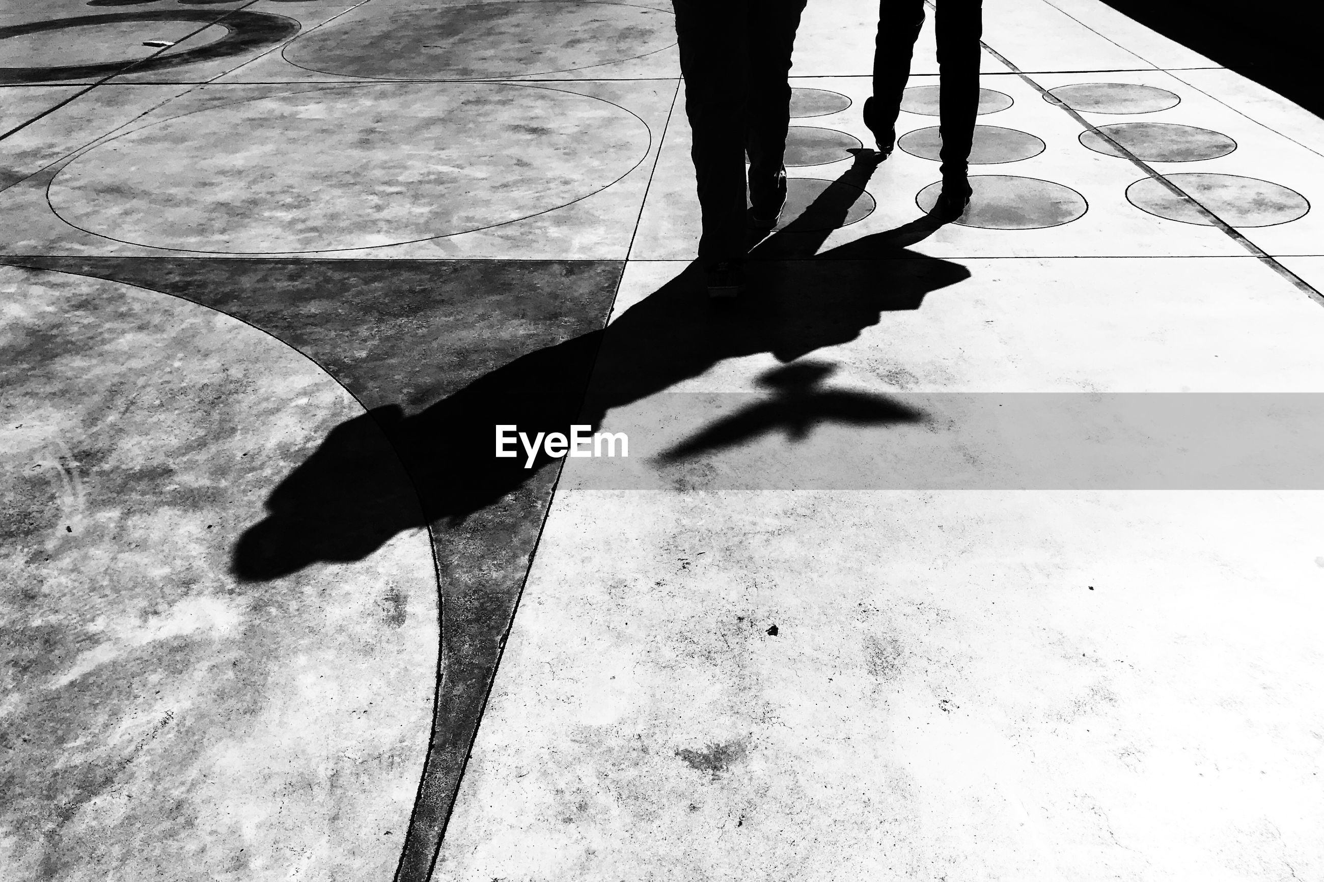low section, one person, real people, shadow, sunlight, body part, human body part, standing, day, human leg, high angle view, lifestyles, nature, walking, unrecognizable person, men, outdoors, leisure activity, flooring, human foot, focus on shadow, tiled floor