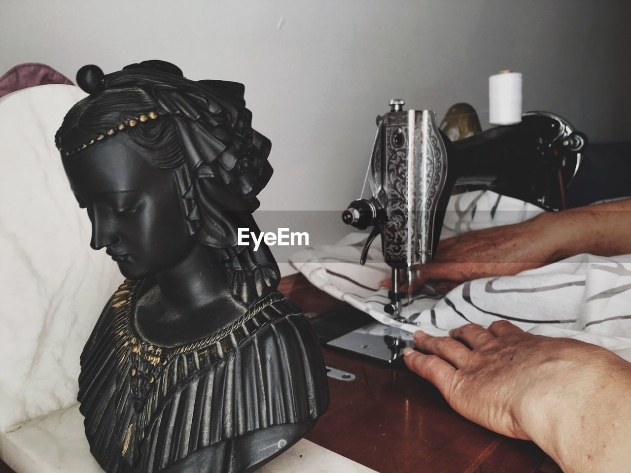 High Angle View Of Statue By Cropped Woman Using Sewing Machine