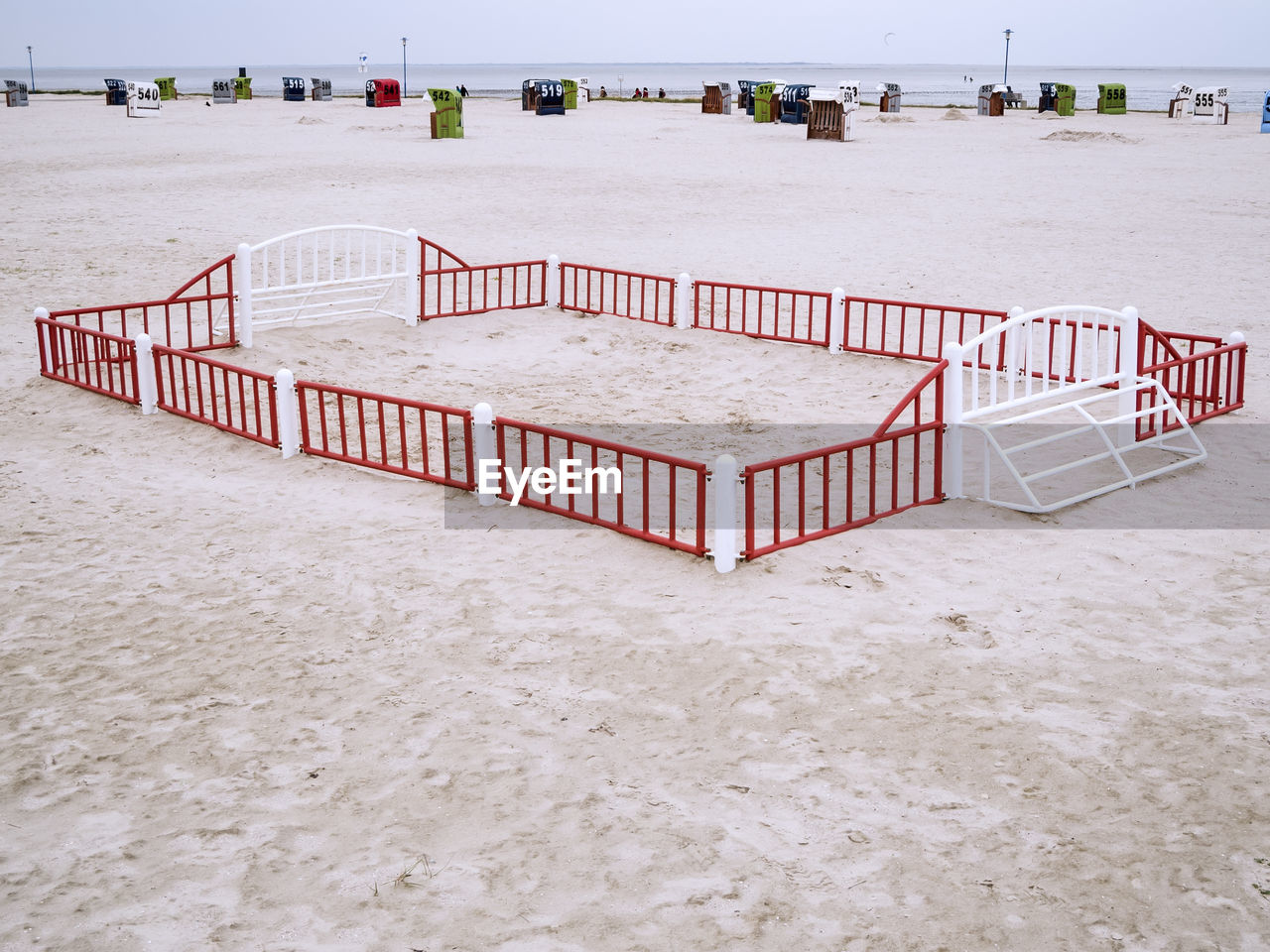 North sea beach with a small fenced beach ball field and view over the wadden sea to the horizon.