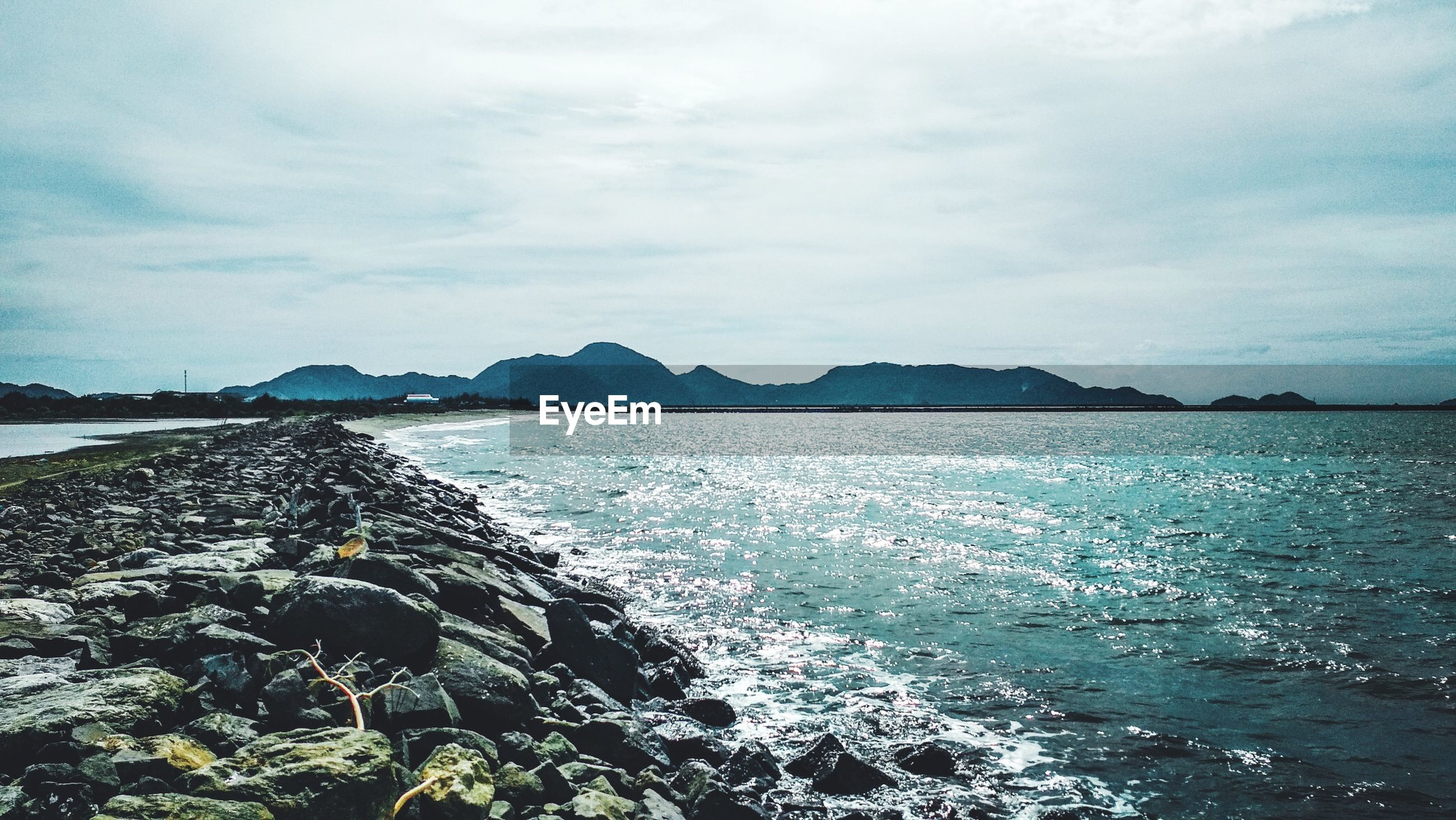 SCENIC VIEW OF SEA BY MOUNTAIN AGAINST SKY