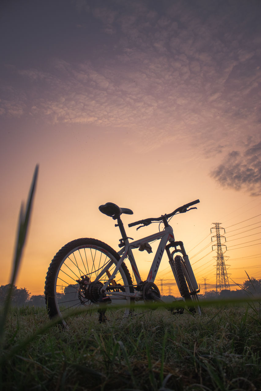 SILHOUETTE OF BICYCLE ON FIELD AGAINST SKY