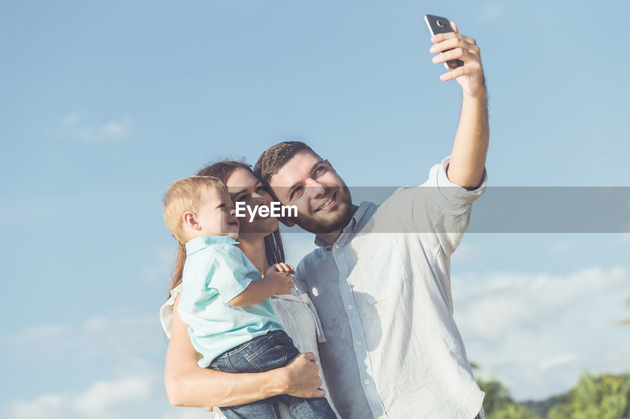 Family taking selfie through mobile phone while standing against sky