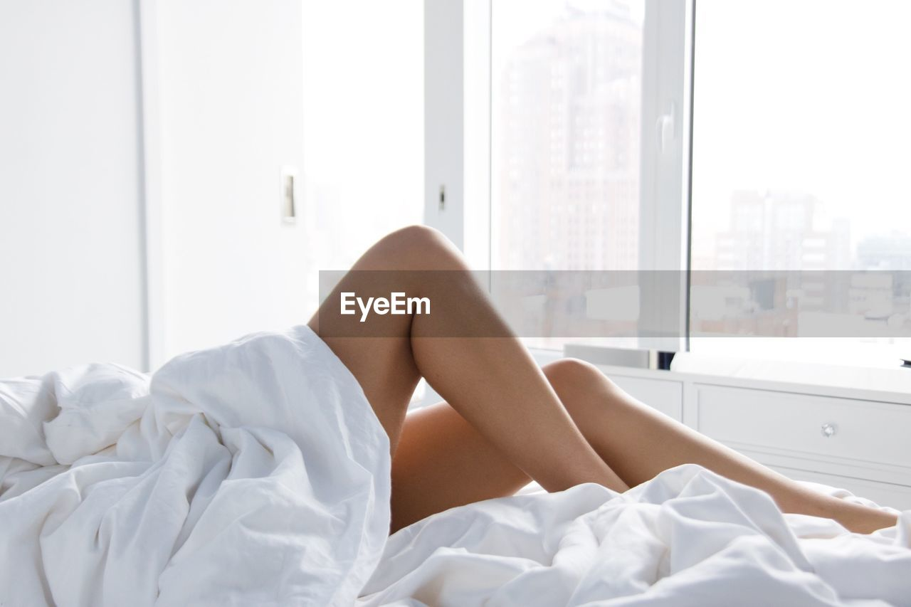 Low section of seductive women relaxing on bed