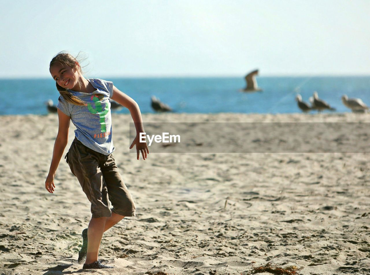 Happy Girl Dancing On Sand At Beach Against Sea During Sunny Day