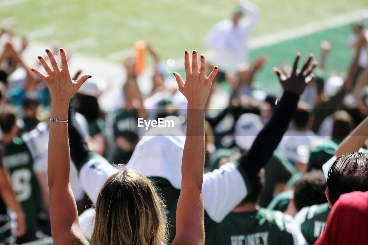 Crowd With Arms Raised At Stadium