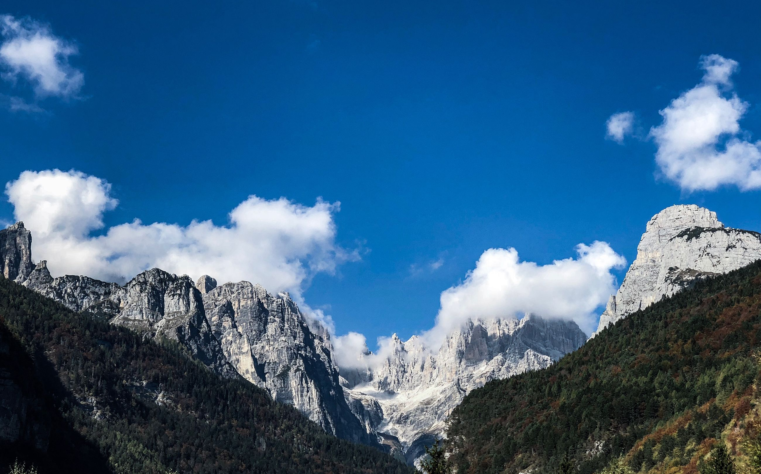 LOW ANGLE VIEW OF PANORAMIC SHOT OF MOUNTAINS AGAINST BLUE SKY