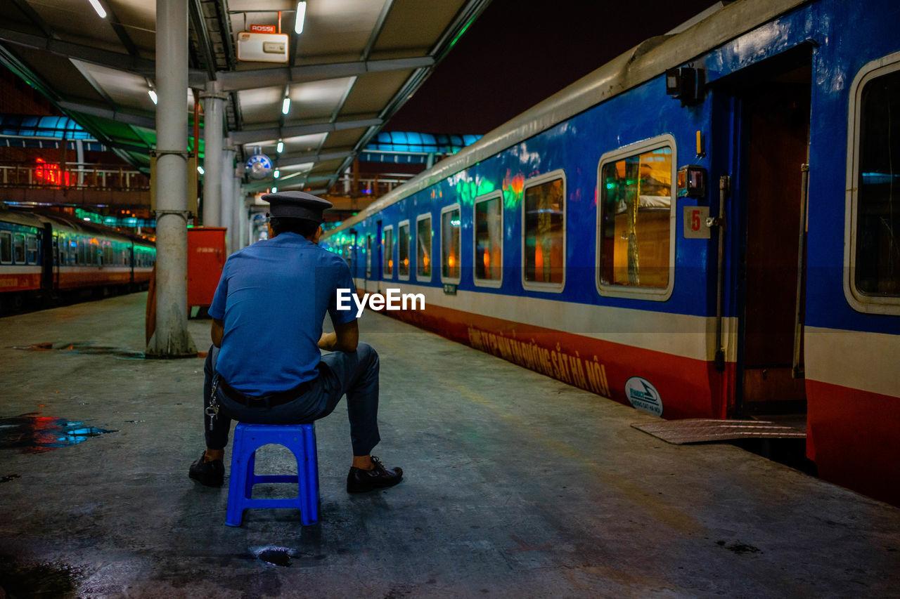 REAR VIEW OF MAN SITTING AT TRAIN