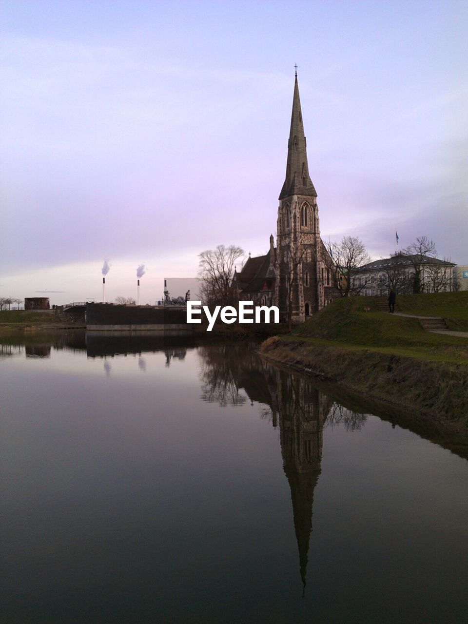 Reflection Of Old Church On Calm Lake Against Sky