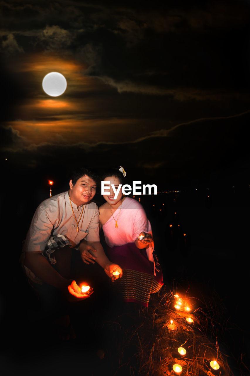 Couple Holding Diyas At Night