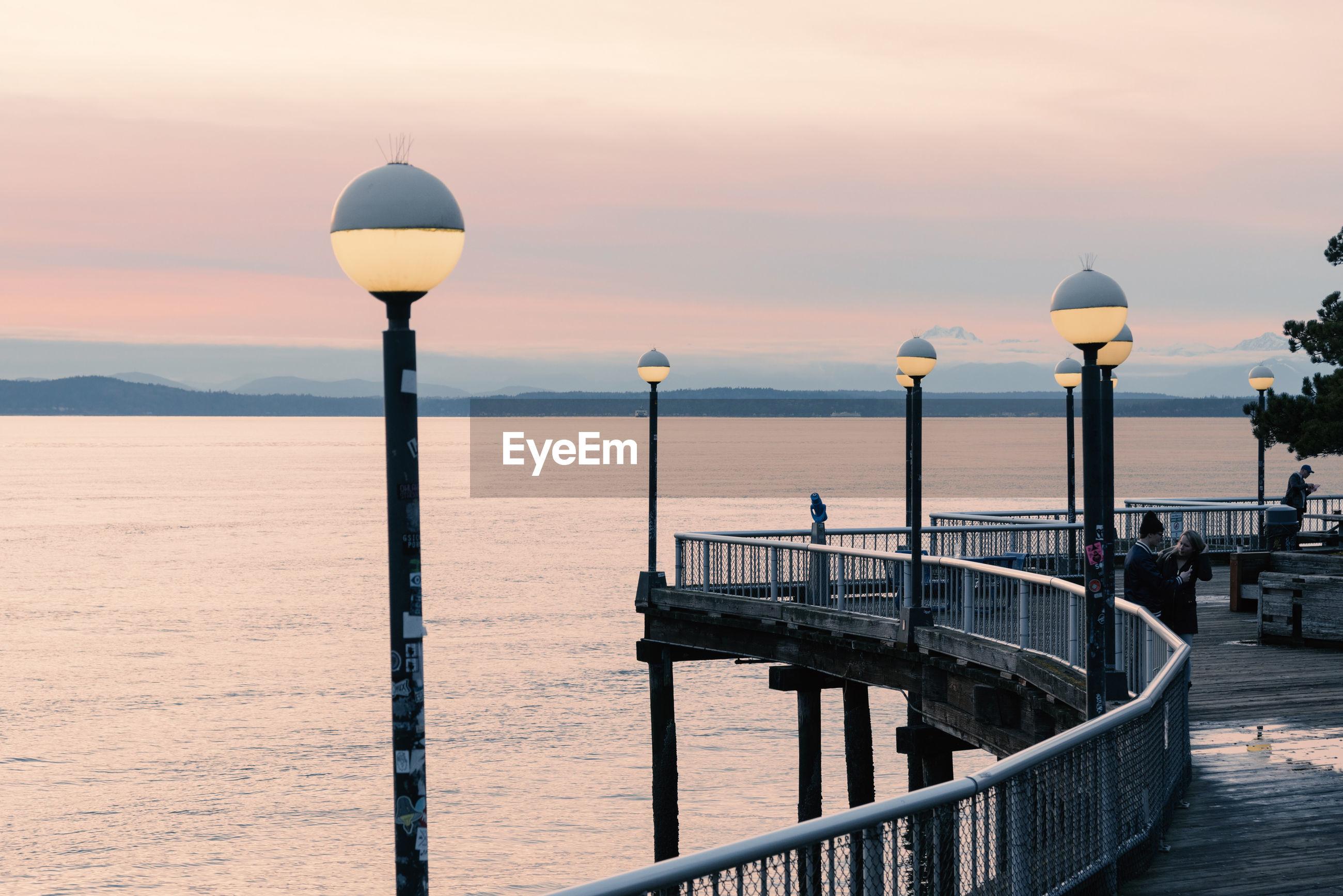 Illuminated street lights on pier by sea