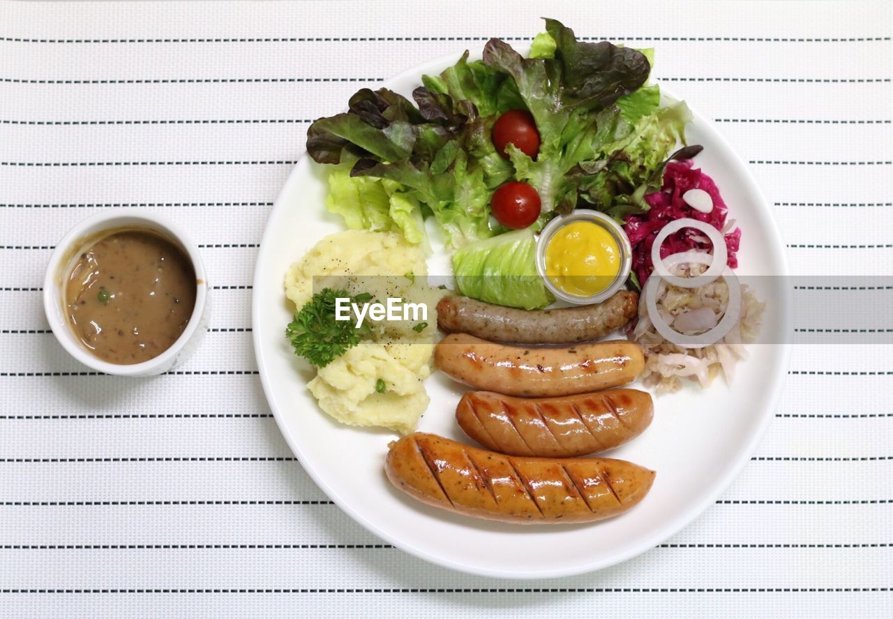 Directly above shot of sausages with salad and mashed potatoes on table