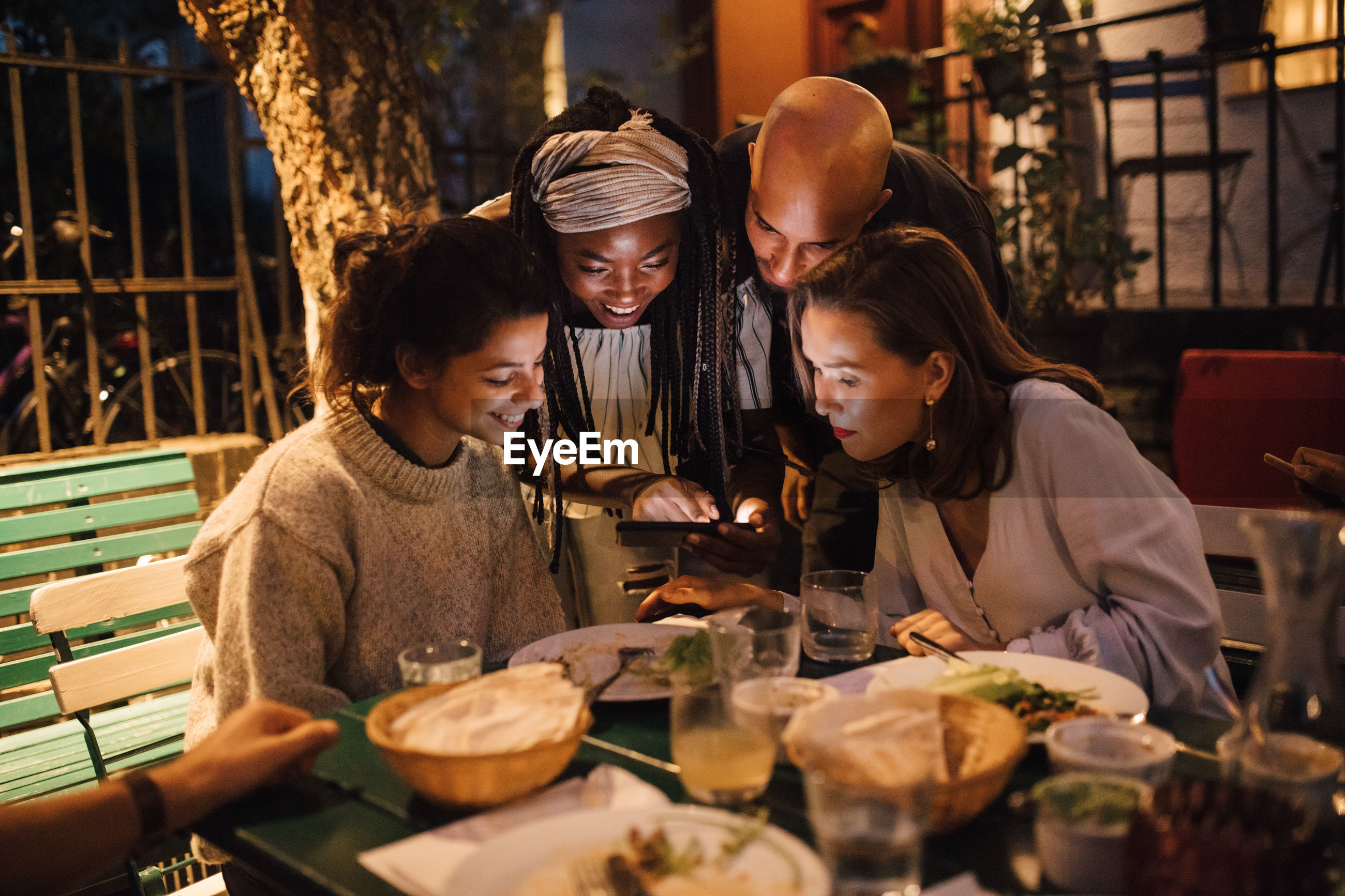Happy young woman showing smart phone to friends at table during dinner party
