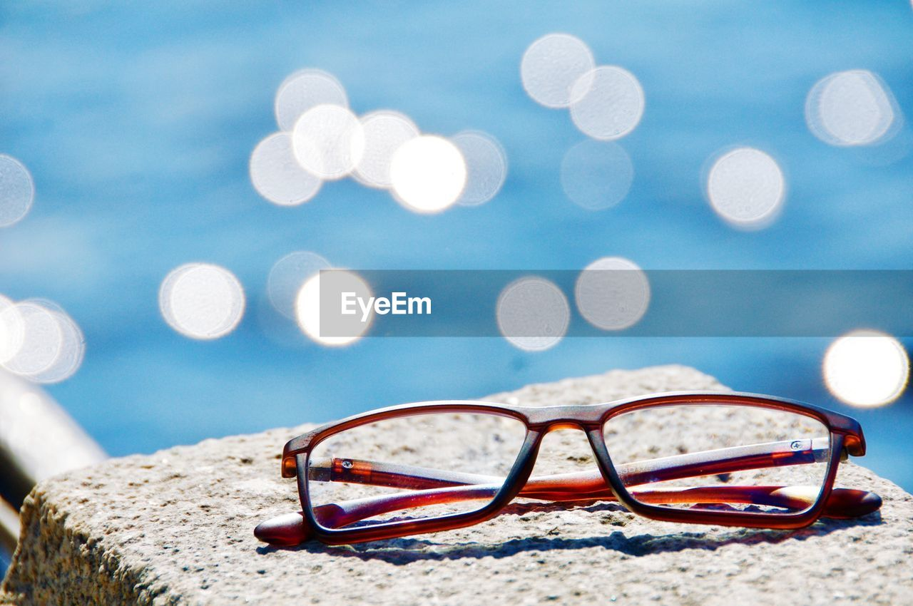glasses, eyeglasses, focus on foreground, close-up, sunglasses, personal accessory, still life, fashion, no people, nature, land, beach, sand, blue, eyewear, glass - material, outdoors, day, selective focus, transparent