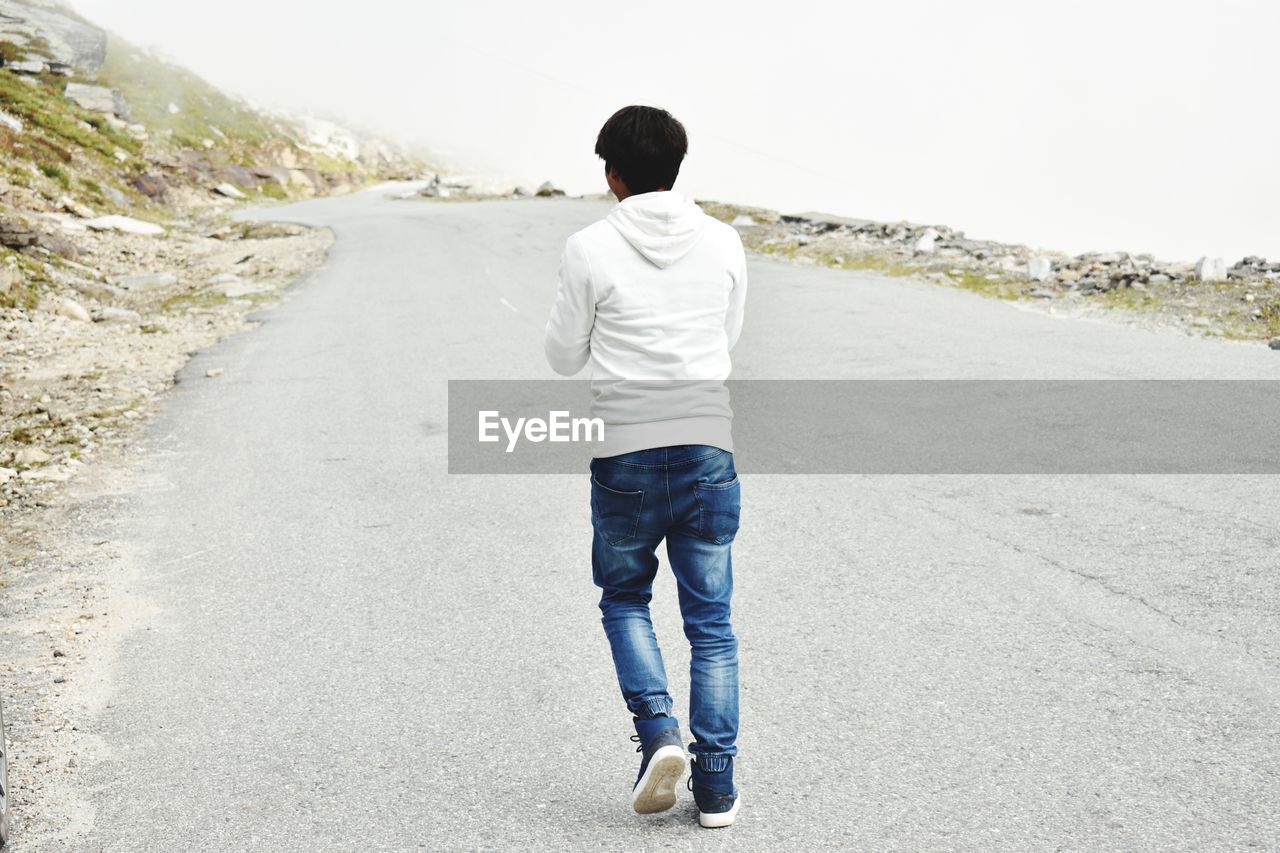 rear view, one person, casual clothing, road, full length, real people, leisure activity, lifestyles, men, day, the way forward, direction, nature, standing, transportation, walking, city, outdoors, males, jeans, warm clothing, hood - clothing