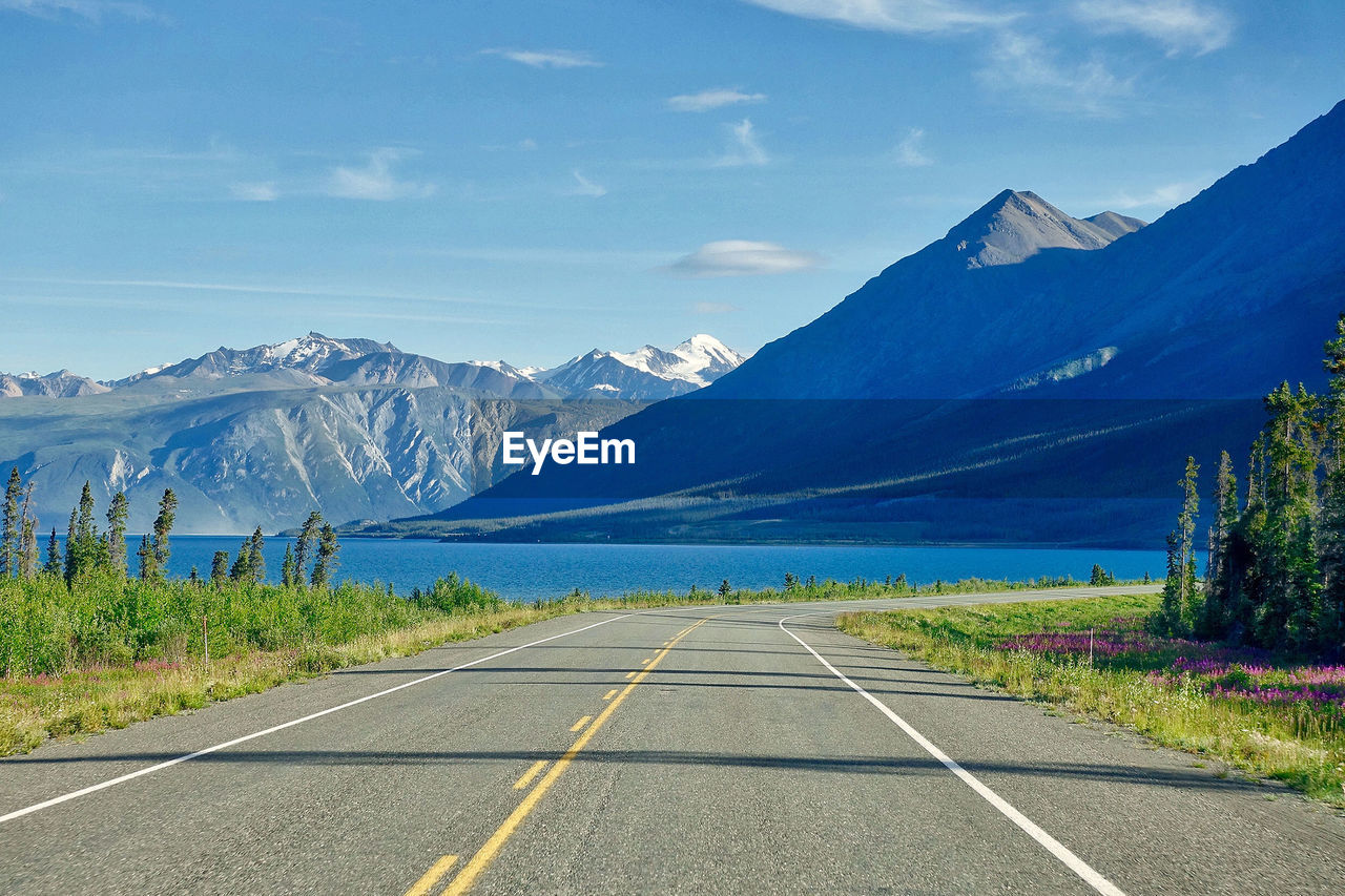 road, mountain, transportation, sky, symbol, beauty in nature, direction, the way forward, scenics - nature, marking, road marking, tranquil scene, no people, diminishing perspective, sign, mountain range, tranquility, nature, cloud - sky, non-urban scene, outdoors, dividing line, long