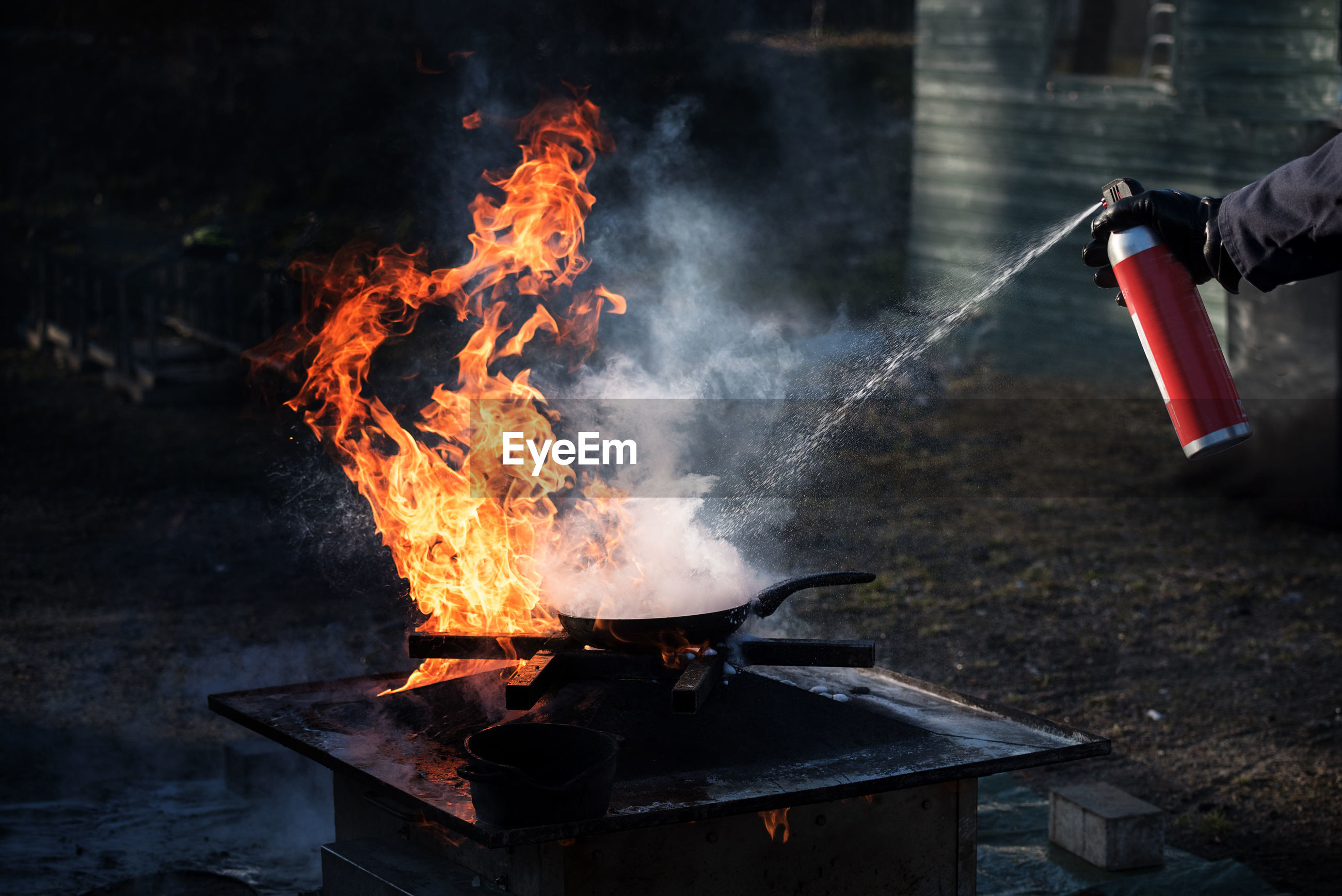 Close-up of cropped hand extinguishing fire on barbecue grill