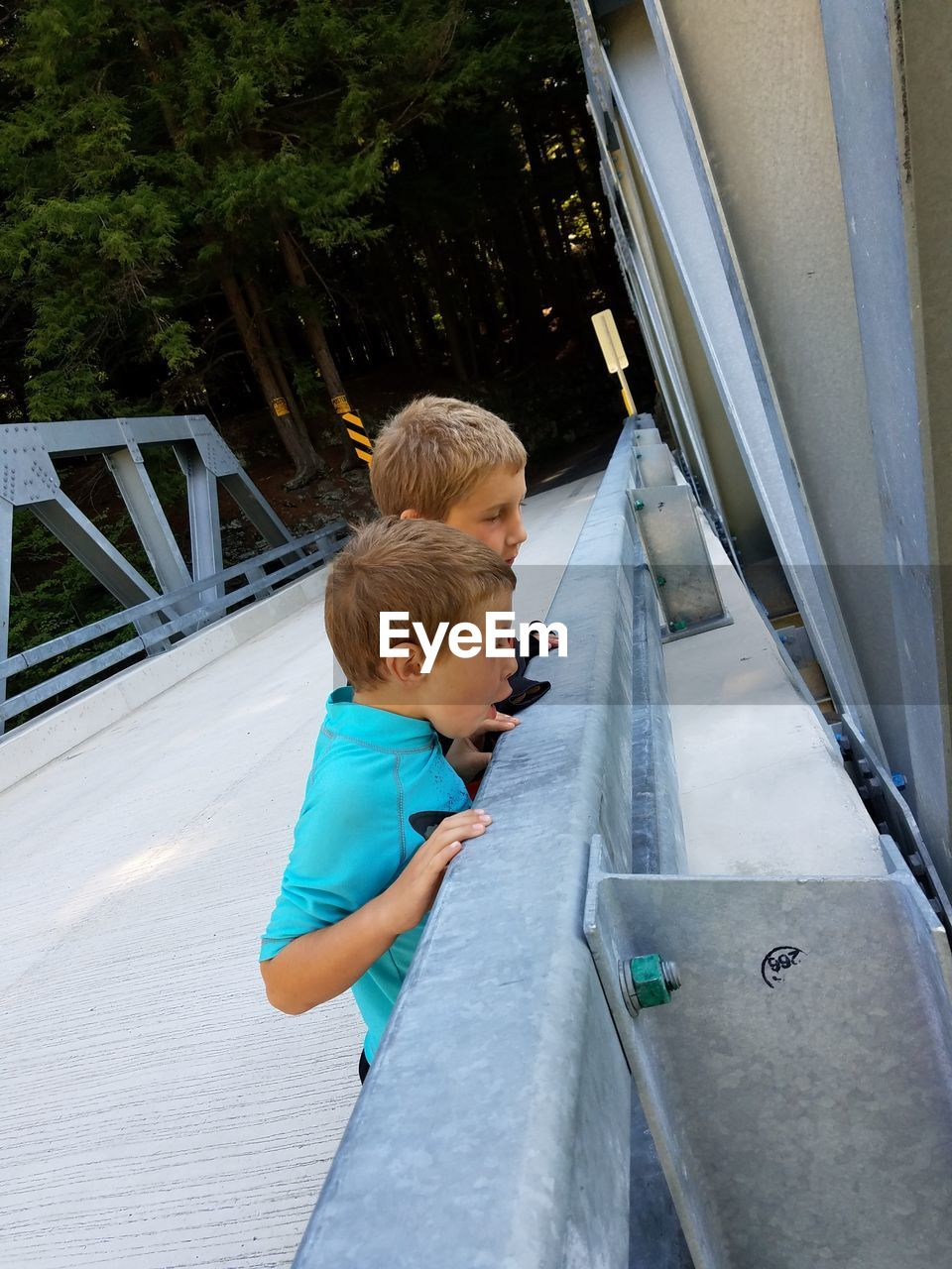 Boys Leaning On Railing While Standing On Bridge