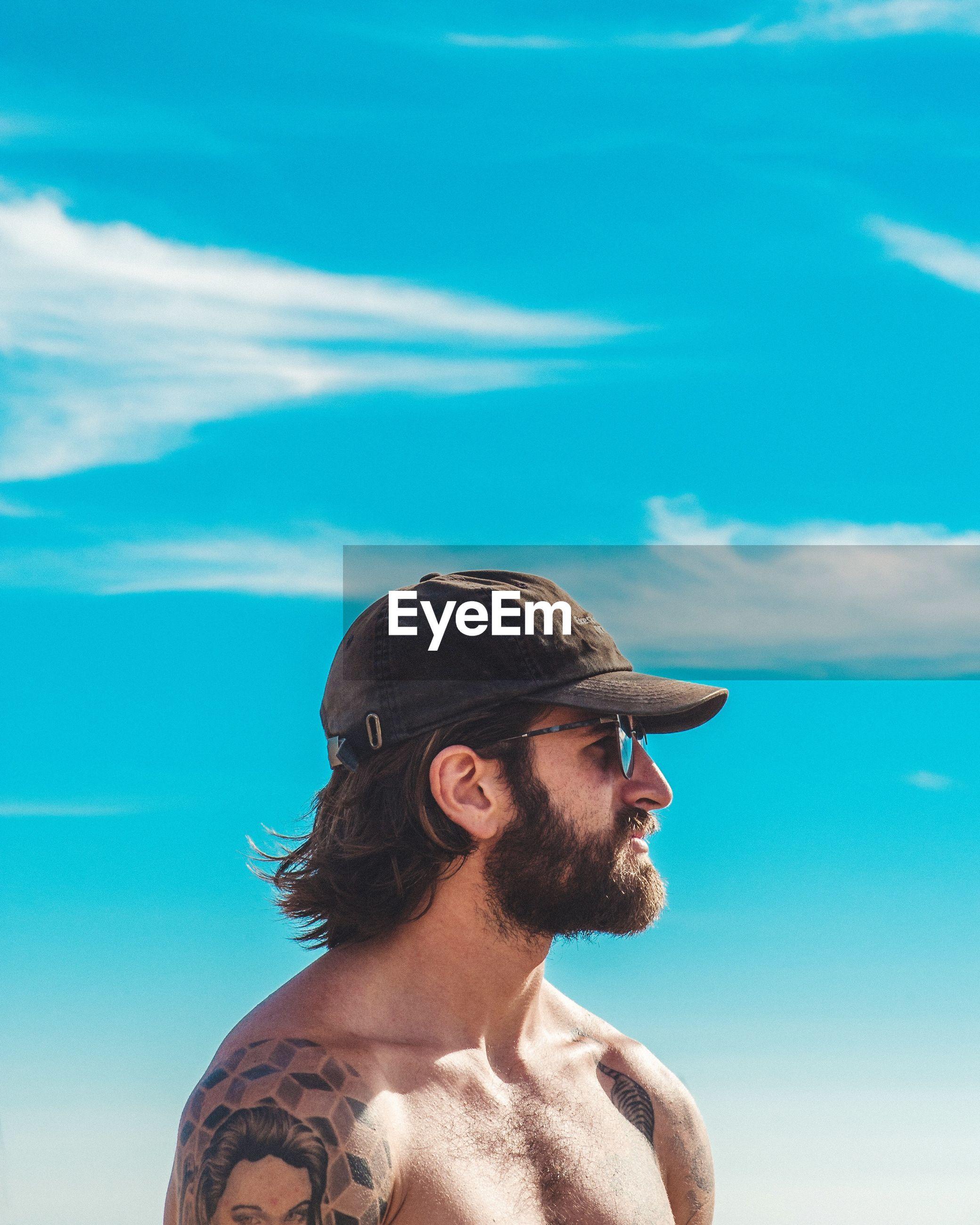 Shirtless man wearing cap against blue sky