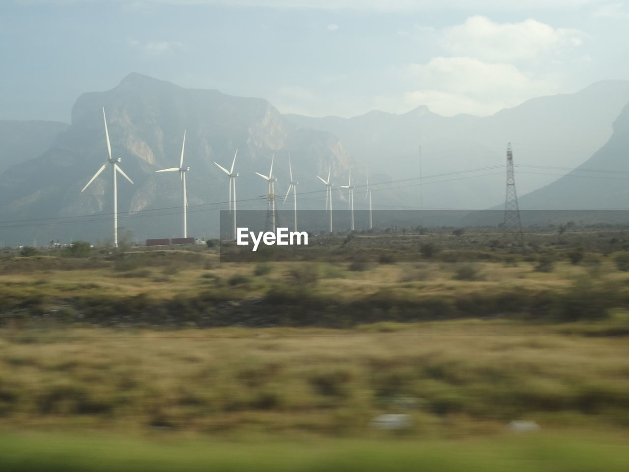 fuel and power generation, mountain, environmental conservation, alternative energy, landscape, wind turbine, field, wind power, renewable energy, no people, nature, day, outdoors, windmill, industrial windmill, sky, mountain range, electricity, rural scene, beauty in nature, grass, scenics, electricity pylon, technology